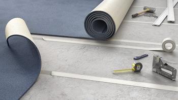 Blauer Teppich wird auf altem Belag verklebt